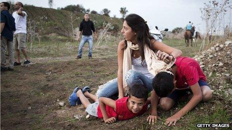 Israeli mother and children crouch down after air raid sirens sound around Tel Aviv (18 Nov)