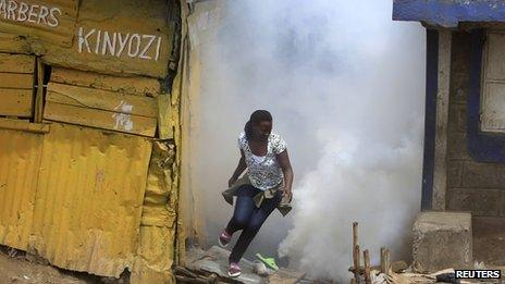 A woman flees from tear gas fired by police in Eastleigh (19 November 2012)