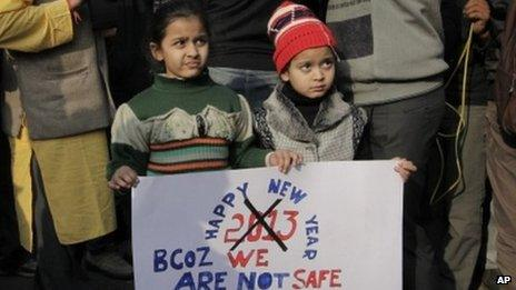 Young Indian girls hold a placard as they participate in a protest in Delhi on 31 Dec 2012
