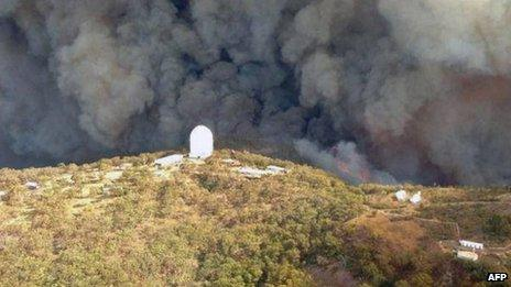 Aerial picture provided by Rural Fire Service (RFS) of New South Wales shows smoke billowing from an out-of-control fire raging towards the Siding Spring Observatory on 13 January 2013