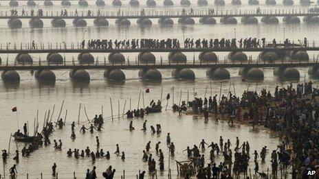 Hindu devotees take a dip at Sangam, the confluence of the Rivers Ganges, Yamuna and mythical Saraswati as others cross a make shift bridge, on one of the most auspicious day Makar Sankranti, the first day of the Maha Kumbh Mela, in Allahabad, India, Monday, Jan. 14, 2013.