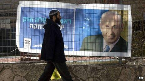 Man walks past election poster of Benjamin Netanyahu, in Kiryat Arba settlement (15/01/13)