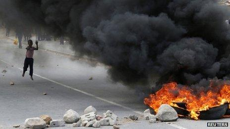 A child runs towards a burning barricade during a strike by farm workers at De Doorns in South Africa on 9 January 2013