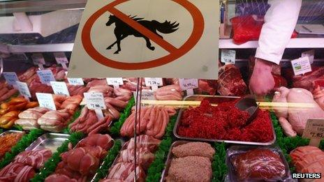 """A butcher works behind a """"no horsemeat"""" sign at Bates Butchers in Market Harborough, central England"""
