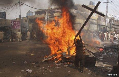 A rioter burns a cross in Lahore, 9 March