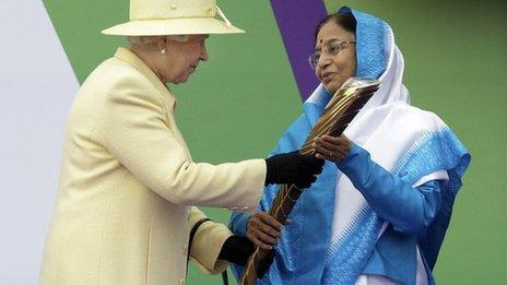 Y Frenhines yn cyflwyno'r baton i Prathibha Devi Singh Patil, Arlywydd India, cyn y Gemau yn Delhi yn 2010a