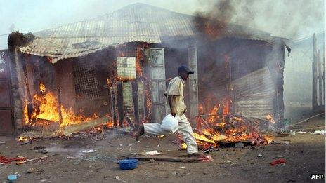 A man runs past a house on fire in Kenya in January 2008