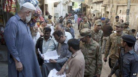 Pakistani soldiers stand guard as staff members of the election commission verify lists of voters in Karachi