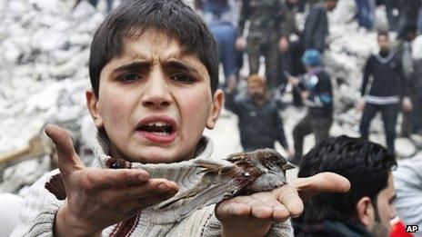 A Syrian boy holds a bird in his hand that he said was injured in an airstrike hit the neighbourhood of Ansari, in Aleppo, Syria, Sunday, Feb. 3, 2013
