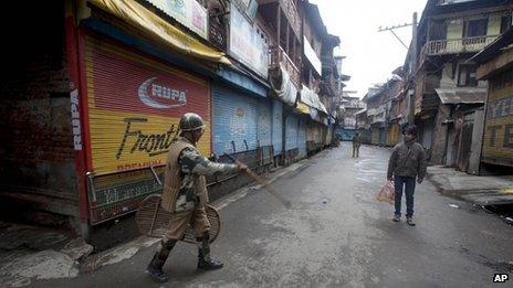 An Indian paramilitary soldier orders a pedestrian to go back during a curfew in Srinagar, India, Thursday, March 14, 2013.