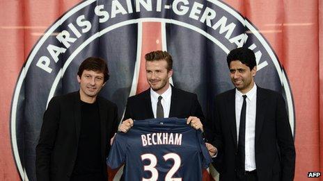 David Beckham flanked by PSG sports director Leonardo (L) and PSG Qatari president Nasser Al-Khelaifi