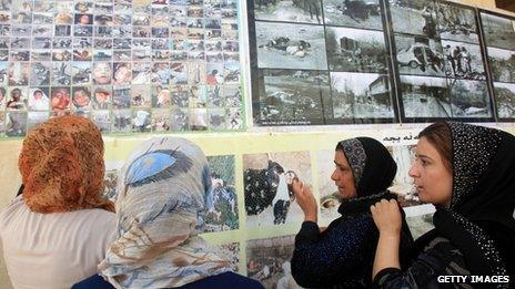 Women weep as they look at photos of the dead in Halabja