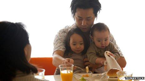 Father helping feed children