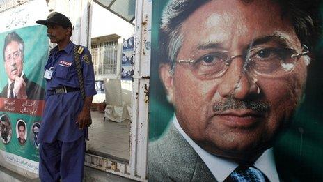 """A security man stands guard at the entrance of former president Pervez Musharraf""""s campaign office, decorated with posters in Karachi"""