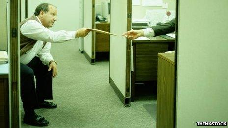Two men in a badly lit cubicle office
