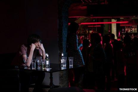 Man sitting alone at table in bar