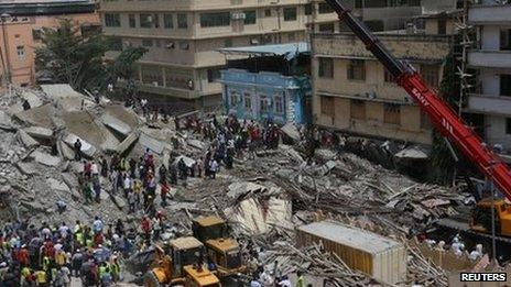 Rescuers search for survivors amongst the rubble of a collapsed building in the Kariakoo district of central Dar es Salaam (29 March 2013)
