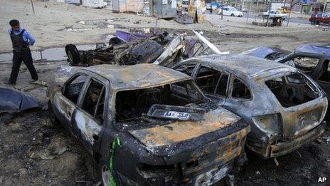 Iraqi policeman inspects burnt out cars in aftermath of car bomb attack in Habibiya neighborhood of eastern Baghdad, Iraq.