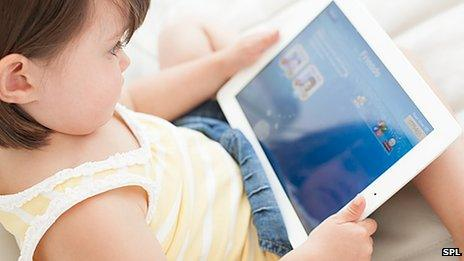 Young child playing with a tablet