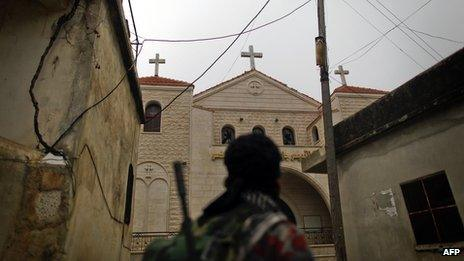 A rebel fighter looks at a church in Halassamiya (24 November 2012)
