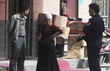 Local people speak to a police officer in Kashgar (25 April 2013)