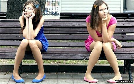 Generic image of two girls, sitting on a park bench, facing away from each other as though after an argument