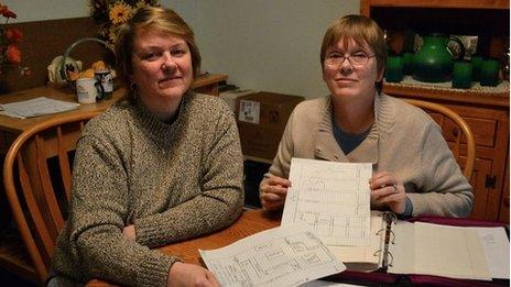 Women hold up paperwork