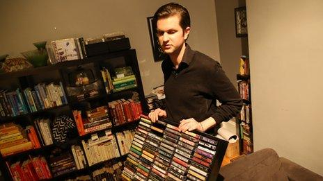Man holds up a rack of cassette tapes.