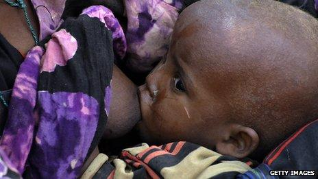 The child of a Somali refugee being breastfed by its mother at a Kenyan refugee camp