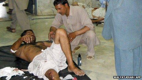 An injured Pakistani blast victim receives assistance at a hospital following bomb attacks in northwestern Malakand region (May 17, 2013)