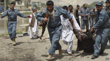 Afghan policemen evacuate a wounded person after a suicide bomber struck outside provincial council headquarters in Pul-e Khomri, Baghlan province, northern Afghanistan (20 May 2013)