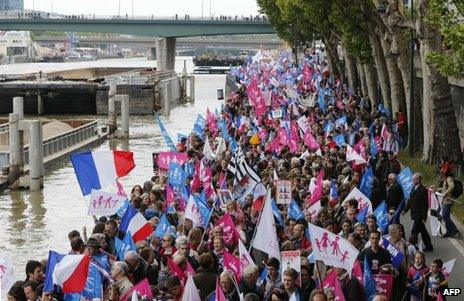 Demonstrators march along the Seine in Paris, 26 May