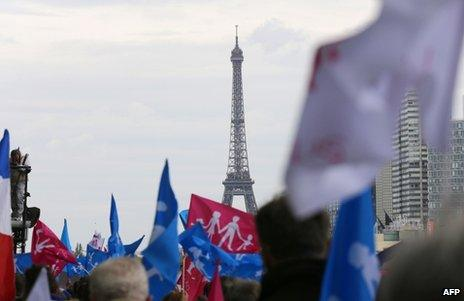 Demonstrators march through Paris with the Eiffel Tower in the background, 26 May
