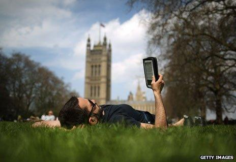 Man reading e-reader near parliament