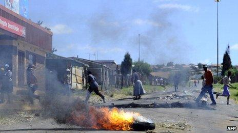 Protesters run away from South African police who fire rubber bullets at them on 16 February 2011, in Wesselton township outside of Ermelo