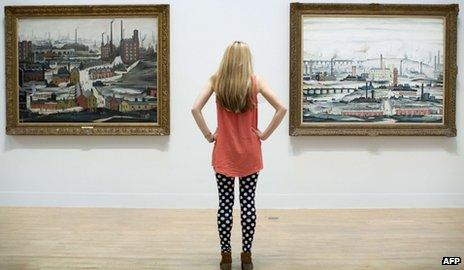 """An employee poses for a picture in front of English artist Laurence Stephen Lowry""""s paintings """"Industrial Landscape (Ashton Under Lyne 1952) (L) and """"Industrial Landscape 1955"""" (R) at the Lowry and the Painting of Modern Life exhibition at Tate Britain in London on June 24, 2013."""