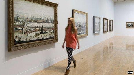 """A museum employee walks past English artist Laurence Stephen Lowry""""s painting """"The Pond 1950"""" at the Lowry and the Painting of Modern Life exhibition at Tate Britain in London on June 24, 2013"""