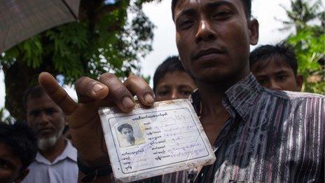 A Rohingya in Ah Nauk Pyin holds up his white ID card