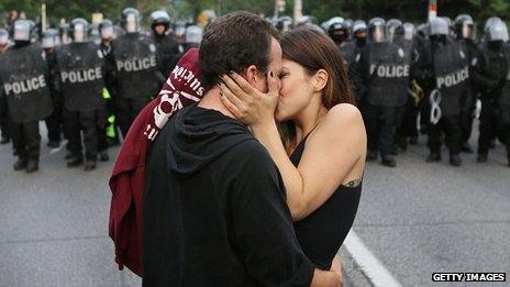 A couple kiss in front of police at a G8 summit protest