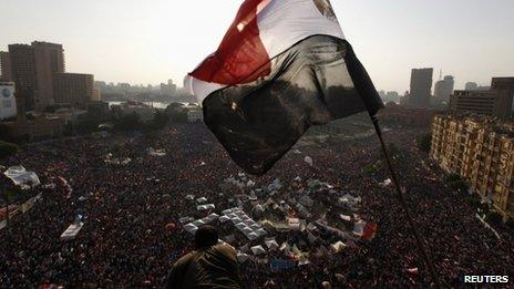 An Egyptian flag flies above protesters in Tahrir Square, Cairo, 30 June