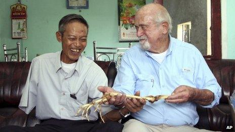 Dr Sam Axelrad, right, hands over arm bones belonging to former North Vietnamese soldier Nguyen Quang Hung at Hung's house in Gia Lai province, Vietnam on 1 July 2013
