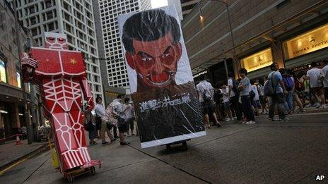 """A defaced picture of of Hong Kong""""s Chief Executive Leung Chun-ying is displayed in a downtown street during an annual pro-democracy protest in Hong Kong Monday, July 1, 2013"""