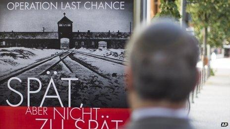 """The Simon Wiesenthal Center's Efraim Zuroff stands in front of a poster reading """"Operation last chance - late but not too late"""" on 23 July 2013"""