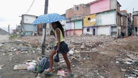 A girl walks through the Manguinhos favela on 23 July 2013