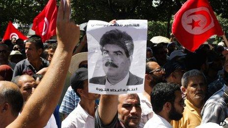 Supporters of the Islamist Ennahda movement demonstrate as they chants slogans and hold a picture of assassinated politician Mohammed Brahmi during a demonstration in Tunis, Tunisia, Friday 26 July 2013