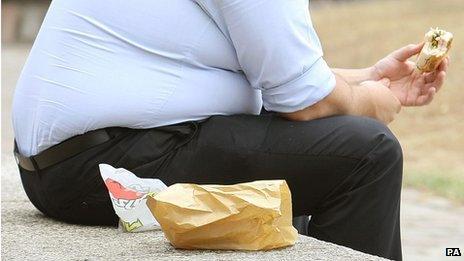 Overweight man eats sandwich