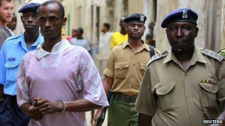 Ali Babitu Kololo in handcuffs being escorted by police