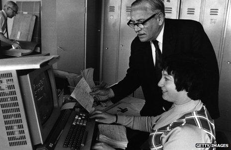 A man leans over the desk of a woman using one of the early word processors