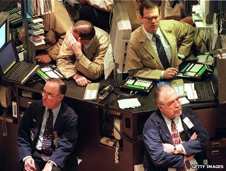 Four traders look on somewhat idly, some of them watching computers