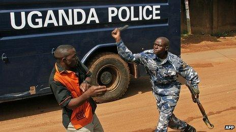 An Uganda policeman batons a journalist in Kampala on 28 May 2013, outside the Daily Monitor and Red Pepper newspapers, which were closed on May 20 by armed police
